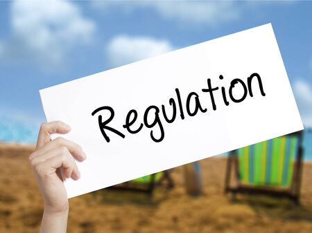 Regulation Sign on white paper. Man Hand Holding Paper with text. Isolated on holiday background. Business concept. Stock Photo