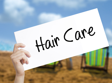 comb: Hair Care Sign on white paper. Man Hand Holding Paper with text. Isolated on holiday background.  Business concept. Stock Photo