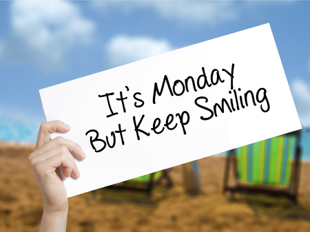 acceptable: Its Monday But Keep Smiling Sign on white paper. Man Hand Holding Paper with text. Isolated on holiday background.  Business concept. Stock Photo