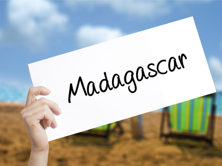 fort dauphin: Madagascar Sign on white paper. Man Hand Holding Paper with text. Isolated on holiday background.   Business concept. Stock Photo