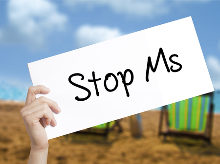 spasms: Stop Ms Sign on white paper. Man Hand Holding Paper with text. Isolated on holiday background.   Business concept. Stock Photo