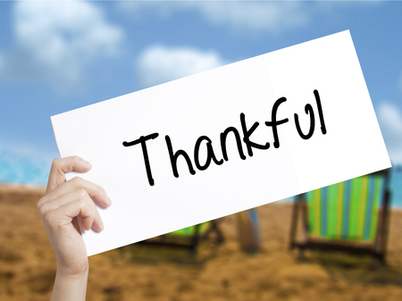 Thankful  Sign on white paper. Man Hand Holding Paper with text. Isolated on holiday background.  Business concept. Stock Photo