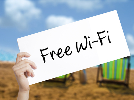e commerce: Free Wi-Fi  Sign on white paper. Man Hand Holding Paper with text. Isolated on holiday background.   Business concept. Stock Photo Stock Photo
