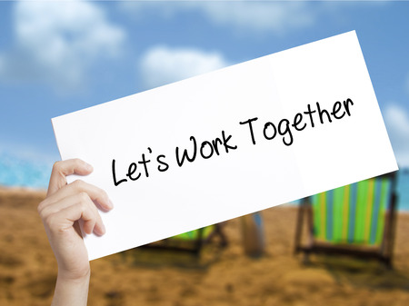 Lets Work Together Sign on white paper. Man Hand Holding Paper with text. Isolated on holiday background.  Business concept. Stock Photo