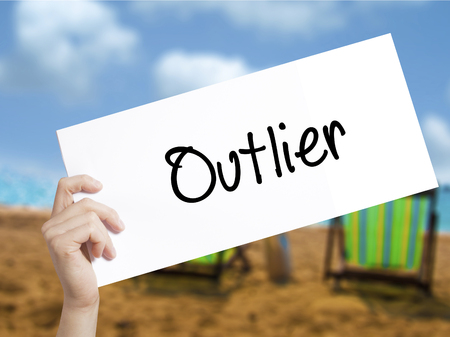 Outlier  Sign on white paper. Man Hand Holding Paper with text. Isolated on holiday background.  Business concept. Stock Photo Stock Photo