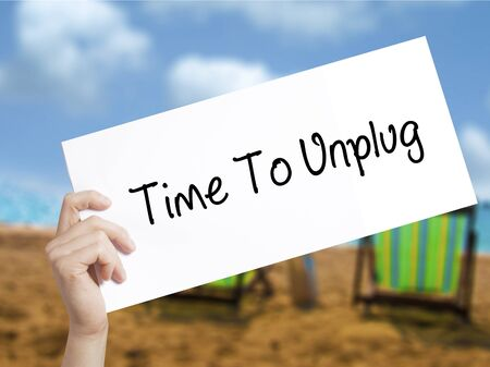 unplugging: Time To Unplug Sign on white paper. Man Hand Holding Paper with text. Isolated on holiday background.   Business concept. Stock Photo