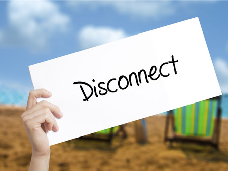 Disconnect Sign on white paper. Man Hand Holding Paper with text. Isolated on holiday background.   Business concept. Stock Photo
