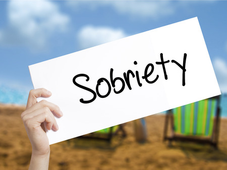 Sobriety Sign on white paper. Man Hand Holding Paper with text. Isolated on holiday background.   Business concept. Stock Photo