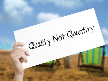 Quality Not Quantity Sign on white paper. Man Hand Holding Paper with text. Isolated on holiday background.   Business concept. Stock Photo