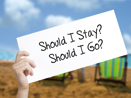 Should I Stay? Should I Go? Sign on white paper. Man Hand Holding Paper with text. Isolated on holiday background.   Business concept. Stock Photo