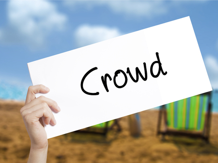 differentiation: Crowd Sign on white paper. Man Hand Holding Paper with text. Isolated on holiday background.   Business concept. Stock Photo