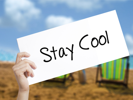 Stay Cool   Sign on white paper. Man Hand Holding Paper with text. Isolated on holiday background.  Business concept. Stock Photo Reklamní fotografie