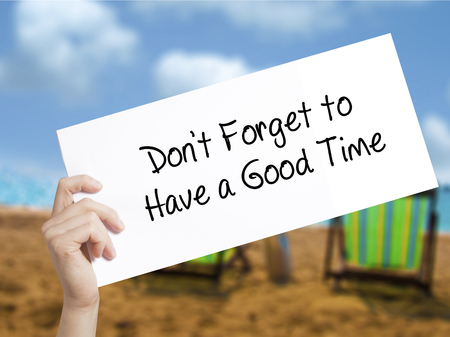 Don't Forget to Have a Good Time Sign on white paper. Man Hand Holding Paper with text. Isolated on holiday background.   Business concept. Stock Photo