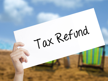 taxable income: Tax Refund Sign on white paper. Man Hand Holding Paper with text. Isolated on holiday background.   Business concept. Stock Photo Stock Photo
