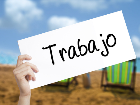 Trabajo  ( work in Spanish) Sign on white paper. Man Hand Holding Paper with text. Isolated on holiday background.  Business concept. Stock Photo