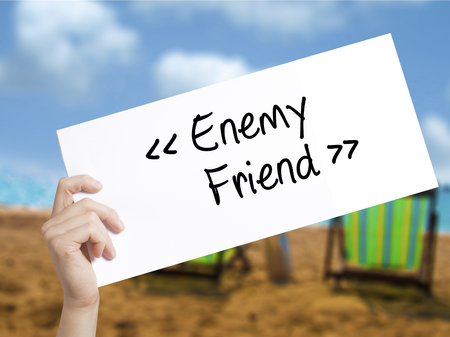 Enemy - Friend Sign on white paper. Man Hand Holding Paper with text. Isolated on holiday background.  Business concept. Stock Photo Stock Photo