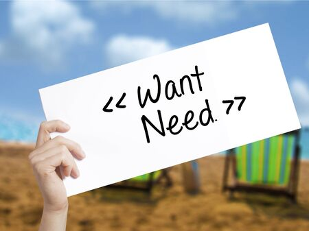 would: Want - Need  Sign on white paper. Man Hand Holding Paper with text. Isolated on holiday background.  Business concept. Stock Photo Stock Photo