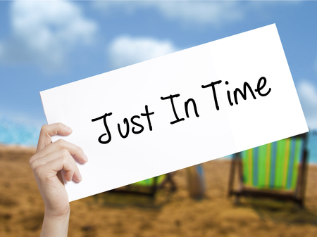 eliminating: Just In Time Sign on white paper. Man Hand Holding Paper with text. Isolated on holiday background.   Business concept. Stock Photo