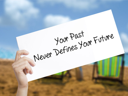 Your Past Never Defines Your Future Sign on white paper. Man Hand Holding Paper with text. Isolated on holiday background.   Business concept. Stock Photo Stok Fotoğraf