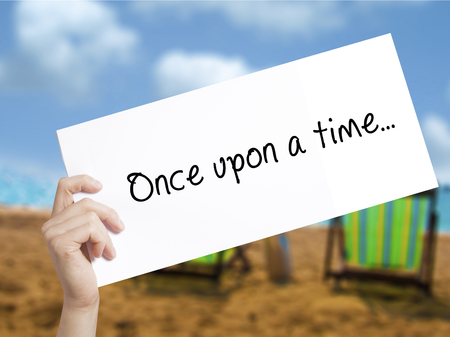 phrase novel: Once upon a time..Sign on white paper. Man Hand Holding Paper with text. Isolated on holiday background.  Business concept. Stock Photo