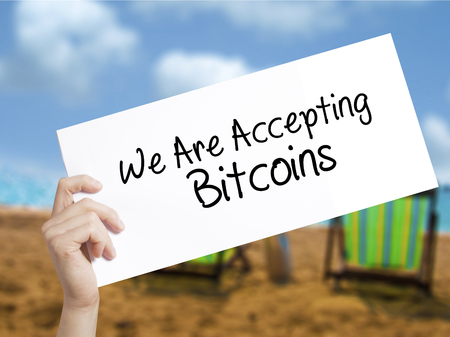 acceptable: We Are Accepting Bitcoins Sign on white paper. Man Hand Holding Paper with text. Isolated on holiday background.   Business concept. Stock Photo Stock Photo