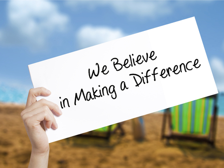 We Believe in Making a Difference Sign on white paper. Man Hand Holding Paper with text. Isolated on holiday background.  Business concept. Stock Photo Stock Photo