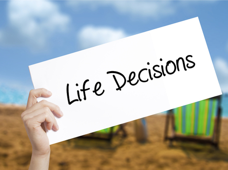 Life Decisions Sign on white paper. Man Hand Holding Paper with text. Isolated on holiday background.  Business concept. Stock Photo