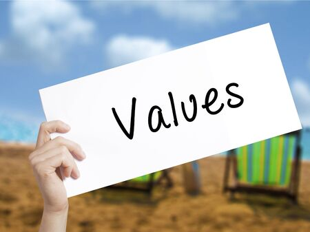 Values Sign on white paper. Man Hand Holding Paper with text. Isolated on holiday background.  Business concept. Stock Photo