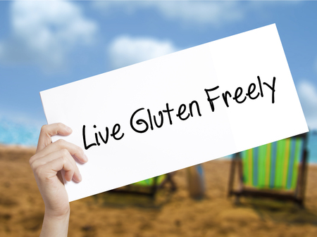 Live Gluten Freely Sign on white paper. Man Hand Holding Paper with text. Isolated on holiday background.  Business concept. Stock Photo