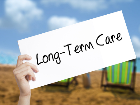 Long-Term Care Sign on white paper. Man Hand Holding Paper with text. Isolated on holiday background.   Business concept. Stock Photo Stock Photo