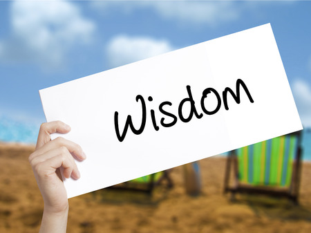 Wisdom Sign on white paper. Man Hand Holding Paper with text. Isolated on holiday background.  technology, internet concept. Banco de Imagens