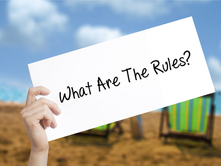 faq's: What Are The Rules?  Sign on white paper. Man Hand Holding Paper with text. Isolated on holiday background.   Business concept. Stock Photo