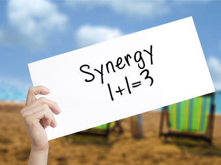 Synergy concept 1+1=3 Sign on white paper. Man Hand Holding Paper with text. Isolated on holiday background.  Business concept. Stock Photo