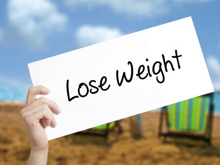 Lose Weight Sign on white paper. Man Hand Holding Paper with text. Isolated on holiday background.  Business concept. Stock Photo