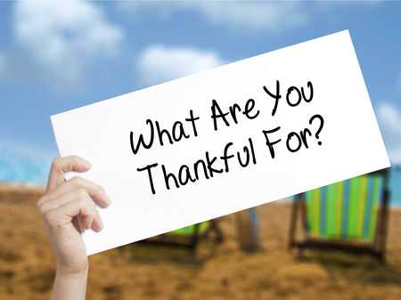 humility: What Are You Thankful For? Sign on white paper. Man Hand Holding Paper with text. Isolated on holiday background.  technology, internet concept.