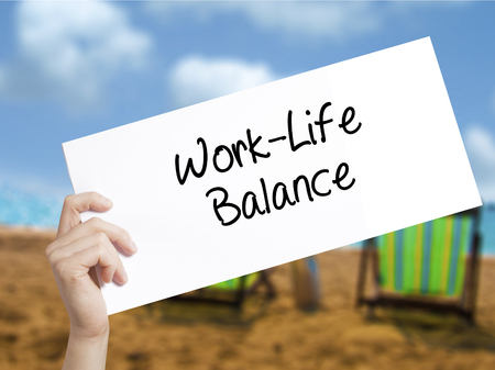 health equity: Work-Life Balance Sign on white paper. Man Hand Holding Paper with text. Isolated on holiday background.   Business concept. Stock Photo