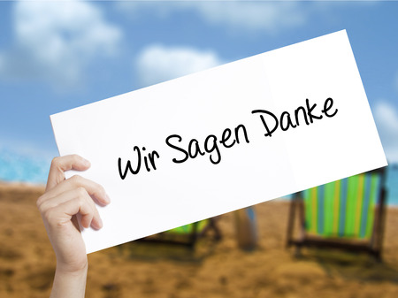 Wir Sagen Danke (We Say Thank You In German)   Sign on white paper. Man Hand Holding Paper with text. Isolated on holiday background.   Business concept. Stock Photo Stock Photo