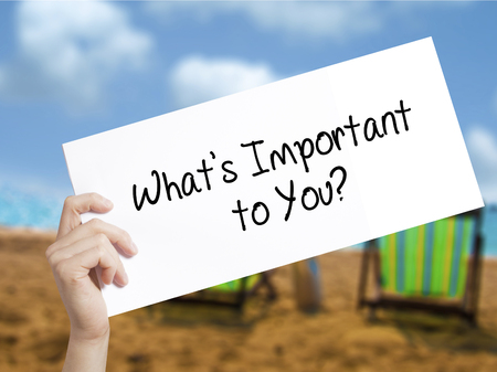 What's Important to You? Sign on white paper. Man Hand Holding Paper with text. Isolated on holiday background.   Business concept. Stock Photo