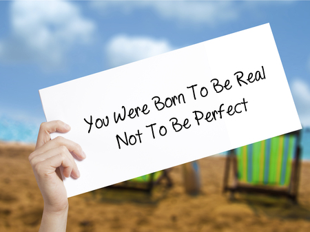 true born: You Were Born To Be Real Not To Be Perfect Sign on white paper. Man Hand Holding Paper with text. Isolated on holiday background.  technology, internet concept. Stock Photo