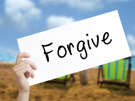 redeeming: Forgive Sign on white paper. Man Hand Holding Paper with text. Isolated on holiday background.  Business concept. Stock Photo