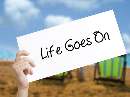 Life Goes On Sign on white paper. Man Hand Holding Paper with text. Isolated on holiday background.   Business concept. Stock Photo
