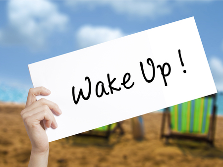 Wake Up Sign on white paper. Man Hand Holding Paper with text. Isolated on holiday background.  Business concept. Stock Photo