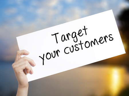 Target your customers Sign on white paper. Man Hand Holding Paper with text. Isolated on sunset background.  Business concept. Stock Photo