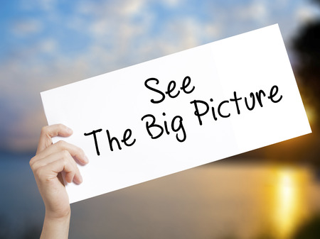 See The Big Picture Sign on white paper. Man Hand Holding Paper with text. Isolated on sunset background.  Business concept. Stock Photo Stock Photo
