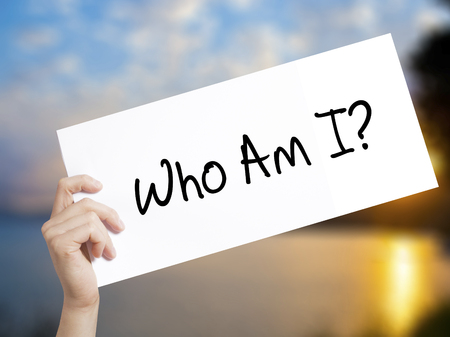 Who Am I? Sign on white paper. Man Hand Holding Paper with text. Isolated on sunset background. Business concept. Stock Photo