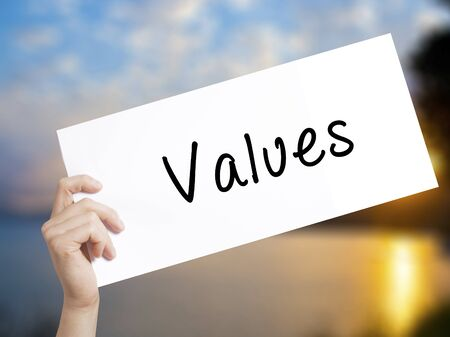 Values Sign on white paper. Man Hand Holding Paper with text. Isolated on sunset background.  Business concept. Stock Photo