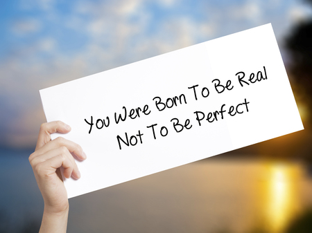 rightful: You Were Born To Be Real Not To Be Perfect Sign on white paper. Man Hand Holding Paper with text. Isolated on sunset background.  technology, internet concept. Stock Photo