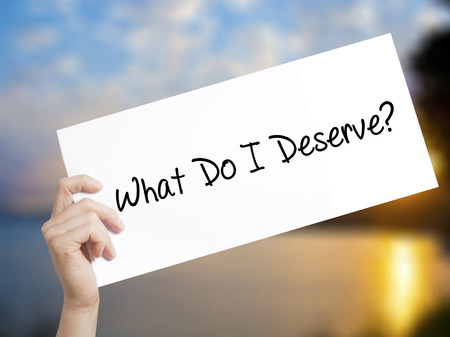 What Do I Deserve? Sign on white paper. Man Hand Holding Paper with text. Isolated on sunset background.  Business concept. Stock Photo