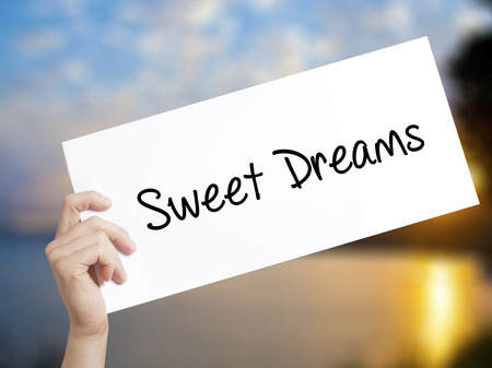 Sweet Dreams Sign on white paper. Man Hand Holding Paper with text. Isolated on sunset background.  technology, internet concept.