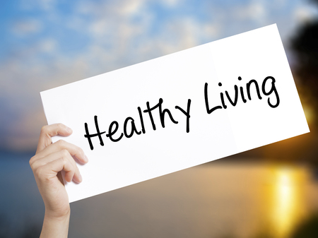 Healthy Living  Sign on white paper. Man Hand Holding Paper with text. Isolated on sunset background.  Business concept. Stock Photo Stock Photo